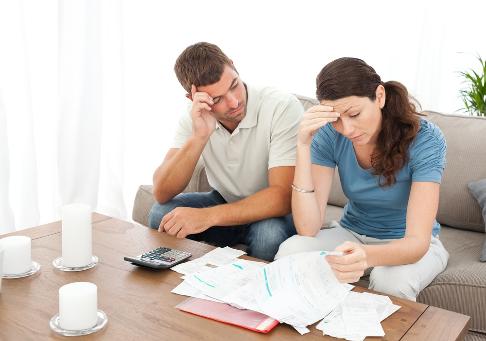 Worried couple doing their accounts in the living room at home.jpeg