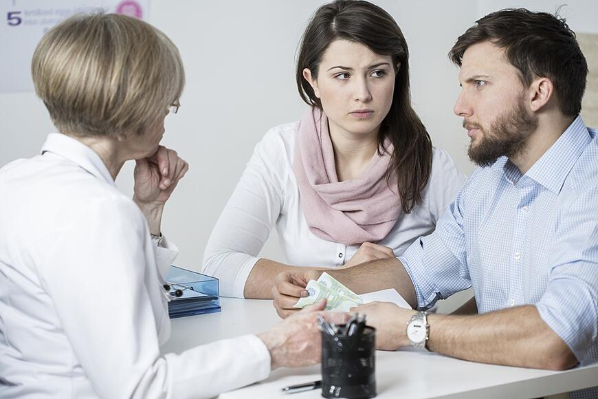 Young worried couple paying to experienced doctor for visit-1.jpeg