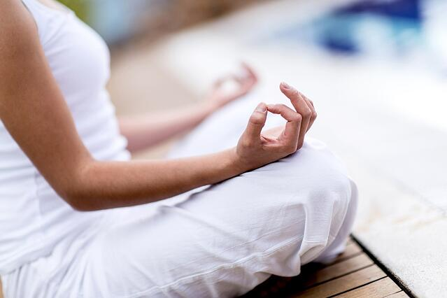 Yoga woman meditating and making a zen symbol with her hand.jpeg