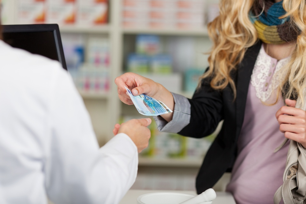 Midsection of pharmacist receiving money from woman for medicines.jpeg
